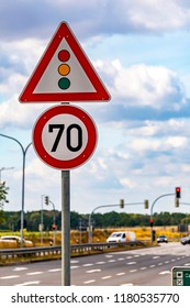 Traffic sign indicating a traffic light and a speed limit in front of a road intersection on a federal road near Berlin, Germany.