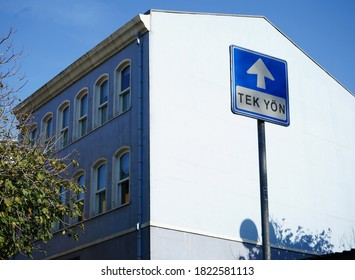 Traffic sign 'Tek yön' meaning one way in Turkish. Beautiful  apartment in the background of the sign.