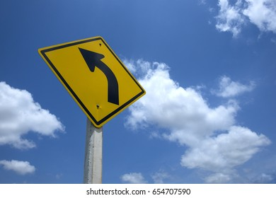 Traffic sign on road, turn left road warning sign against the sky