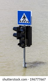 Traffic sign and pedestrian crossing sign in flood