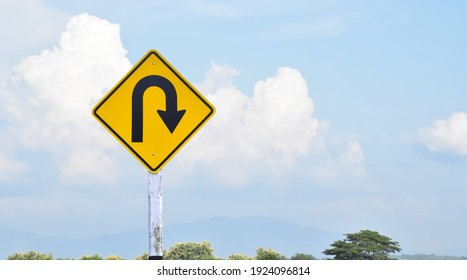 Traffic sign: Right U-turn sign on cement pole beside the rural road with white cloudy bluesky background, copy space. - Shutterstock ID 1924096814