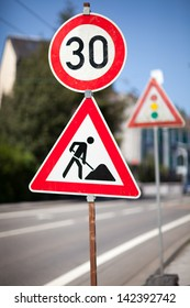 Traffic sign for roadworks ahead at the side of an urban road imposing a reduced speed limit
