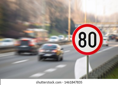 Traffic sign showing 80 km/h speed limit on a highway full of cars