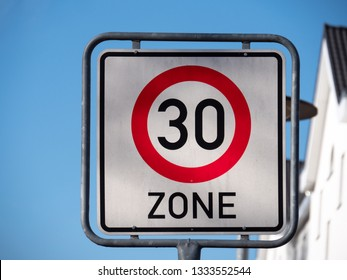 Traffic sign speed limit 30s zone, blue sky.