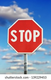 traffic sign - stop - over blue cloudy sky background
