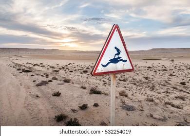 Traffic sign, surf caution. Dakhla, Morocco