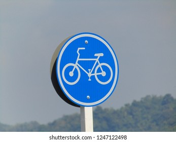 Traffic signs for bicycle lane, mountain and bright blue sky background.
