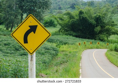 Traffic signs warn, beware of the curve on an empty road and surrounding streets filled with green plants