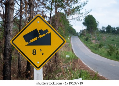 Traffic signs warning up to hill steep road sign to slope a steep climb 8 percent gradient in the road ahead at green grass in the backgroun