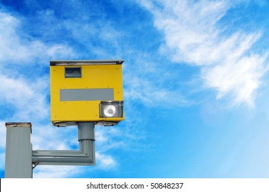 A traffic speed monitoring camera, against a bright blue sky. With space for your text / editorial overlay