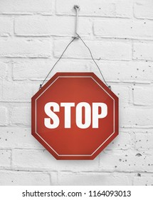 Traffic stop sign metal plate board hanging on white brick background