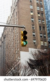 A traffic stoplight with a brownstone building behind. Manhattan, New York City