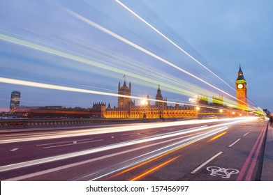 Traffic through London. Big Ben, one of the most prominent symbols of both London and England, as shown at night along with the lights of the cars and busses passing by