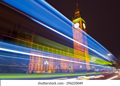 Traffic through London. Big Ben, one of the most prominent symbols of both London and England, as shown at night along with the lights of the cars and buses passing by.
