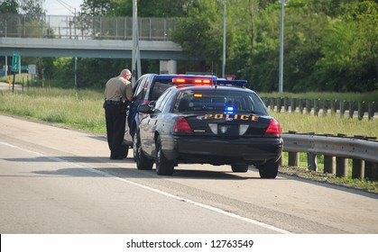 Traffic Ticket Police Vehicle - A police cruiser with the lights flashing has stopped a speeding car along the interstate highway and is issuing a ticket.