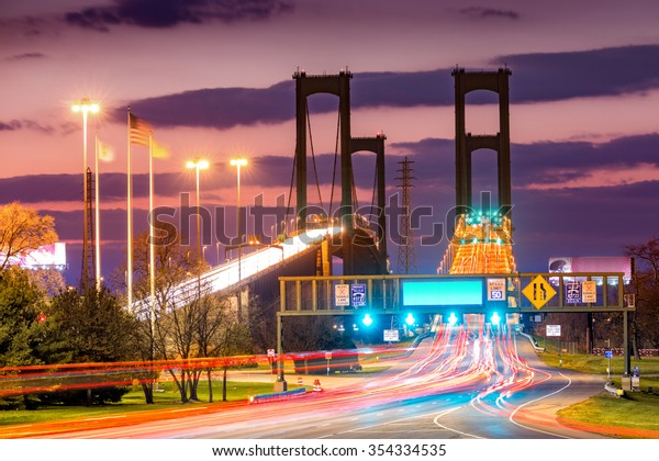 Traffic trails on Delaware Memorial Bridge at dusk. DMB is a set of twin suspension bridges crossing the Delaware River between NJ and DE states, dedicated to WWII, Vietnam and Korean war heroes.