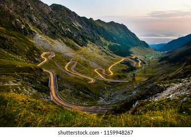 Traffic trails on the Transfagarasan road on the Carpathian Mountains of Romania during the sunrise. Transfagarasan is a paved mountain road crossing the southern section of the Carpathian Mountains.