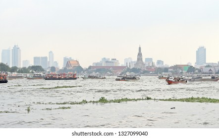 Traffic of transportation by boats in the Choapraya river, major river in Bangkok, Thailand. Taken in front of Wat Arun, Having city view behind as a background.