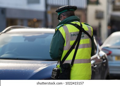traffic warden civil enforcement officer wearing reflective yellow vest issuing fixed penalty parking ticket fine