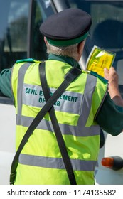 traffic warden civil enforcement officer wearing reflective yellow vest issuing fixed penalty parking ticket fine to white van