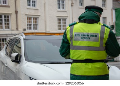 traffic warden civil enforcement officer wearing reflective yellow vest issuing fixed penalty parking ticket fine in typical UK high street