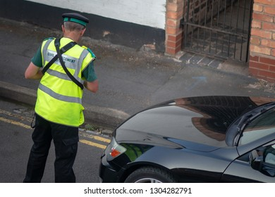 traffic warden or civil enforcement officer putting ticket on black car in UK