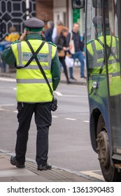 traffic warden otherwise known as civil enforcement officer talks on his phone whilst trying to apply a ticktet to a public transport bus