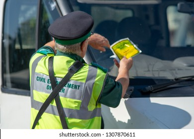 traffic warden in the UK puts parking fine ticket on the window of a white van