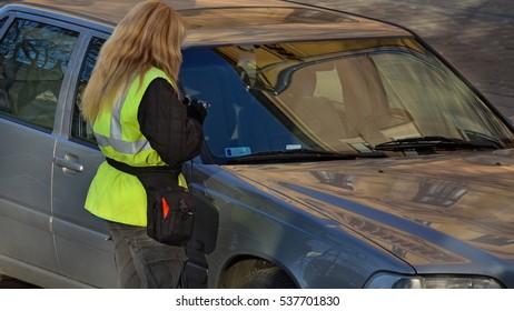 traffic warden woman in yellow jacket checks a car