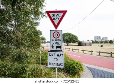 Traffic warning signs for give way, shared zone speed limit 10 km/hr and give way to pedestrians, the image of three traffic signs in one pole.