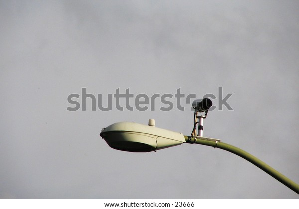 Traffic-control camera with streetlight, with a diffusely cloudy background.