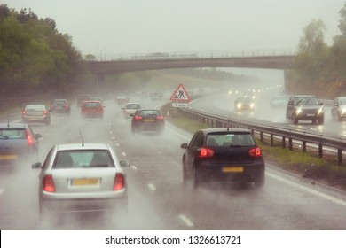 Traffics on a rainy wet highway in fog water spray. Seeing as there's heavy shower on a highway and road condition looks quite dangerous.