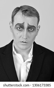 Tragical actor. Man with mime makeup. Mime artist. Mime with face paint. Theatre actor miming. Stage actor miming. Theatrical performance art and pantomime. Comedian or tragedian performer.