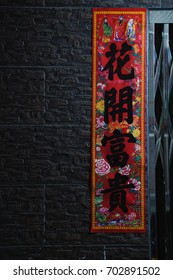 Traidition Chinese red couplet stick on wall in Chinese New Year. The Chinese word means Fortune comes with blooming flowers