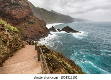 Trail to the beach at Playa de Nogales during storm and rain with tall waves in La Palma, Spain.