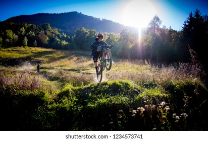 Trail Center Kocevje, Slovenija - October 2 2018: Mountain biker taking of a jump with a fellow rider in the background.