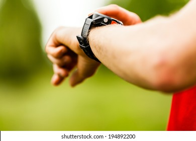 Trail or cross country runner on mountain path looking at wearable sportwatch smart watch, checking performance or heart rate pulse trace. Goal achievement, sport and fitness concept outdoors nature.