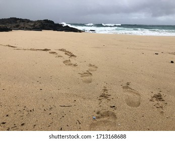 Trail of footprints on a sandy beach on Oahu, Hawaii with massive waves crashing in the background