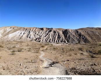 Trail leading toward bad lands in the desert, California