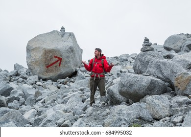 The trail is marked with two large cairns and a giant red arrow painted on a boulder, but this man appears to be lost. Grey, cloudy sky overhead and granite boulder field below.