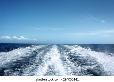 Trail on water surface behind of fast moving motor boat