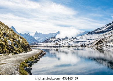 Trail pass and  water reflection of  Bachalpsee - mountain lake above Grindelwald, Switzerland.