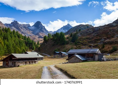 Trail path in Alps between rustic houses cottages in valley. Queyras Regional Park, France, Europe.