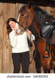 Trail rider with a saddle horse in winter stable