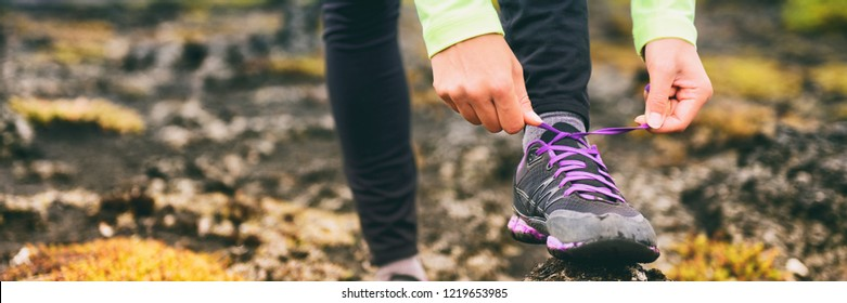 Trail run athlete woman tying laces of running shoes, getting ready for training cardio exercise. Panoramic banner of sneakers.