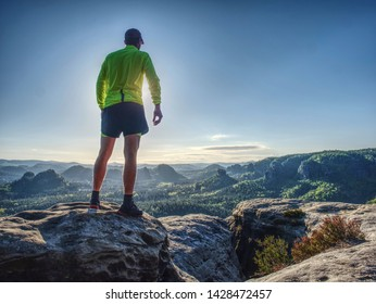 Trail runner athlete man. Slim person training in mountains in cold weather at sunset. Amazing mountain peaks in the background.