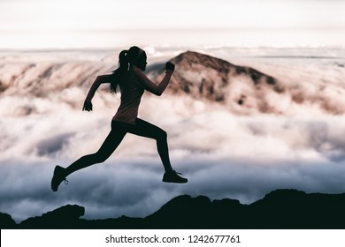 Trail runner athlete silhouette running in mountain summit background clouds and peaks background. Woman training outdoors active fit lifestyle.