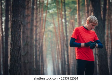 Trail runner athlete stop watch after run in forest