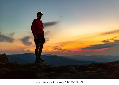 Trail runner with head lamp. Man celebrating sunset on mountain top. Looking at inspiring view. Hiker or climber reached mountain peak, enjoy inspiring landscape on rocky path Karkonosze, Poland