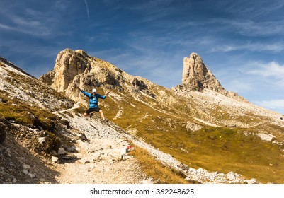 trail runner jumping while running on the track in high mountains with peaks and blue sky